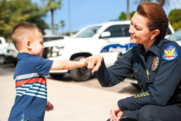 A police woman fist bumps a little kid in front of a line of police cars